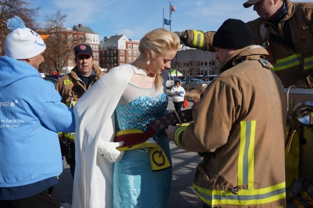 Elsa gets strapped in before climbing the ladder of Quint no. 3 to sing to the race participants. Annual Blue Back Mitten Run, West Hartford, Dec. 7, 2014. Photo credit: Ronni Newton