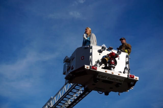 "Elsa sings ""Let It Go"" from high atop the ladder of Quint no. 3 before the start of the Mitten Run. With her is firefighter Brendon Coen. Annual Blue Back Mitten Run, West Hartford, Dec. 7, 2014. Photo credit: Ronni Newton"