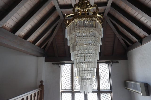 A large chandelier hangs from the foyer's ornate wood ceiling. 2015 Junior League of Hartford Decorator Show House. Photo credit: Ronni Newton