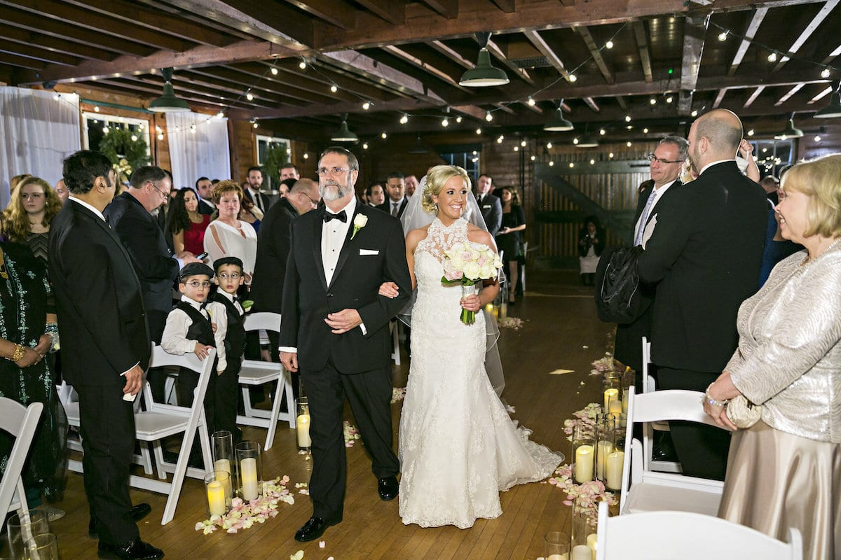 Stephen Bain walks his daughter Sarah down the aisle of the Makeshift Theater space of the Hill-Stead Museum in Farmington. Photo by Danny Kash