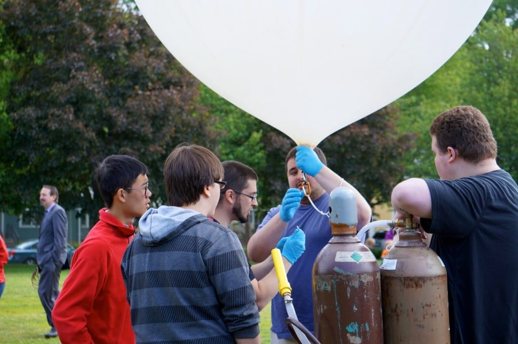 Conard ACES Clun members fill their weather balloon with helium for the launch. Photo credit: Ronni Newton