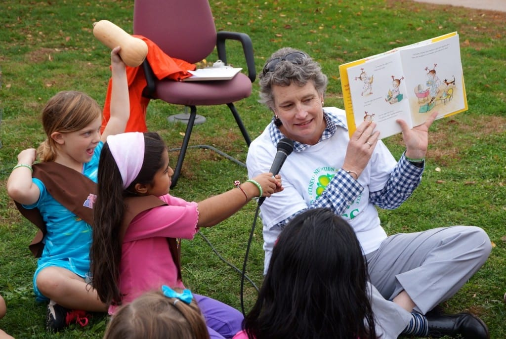 State Sen. Beth Bye reads 'Sophie's Squash' by Pat Zietlow Miller (illus. by Anne Wilsdorf) to a group of Webster Hill students with the help of Lucy and Ruby holding the squash prop and microphone. Photo credit: Ronni Newton
