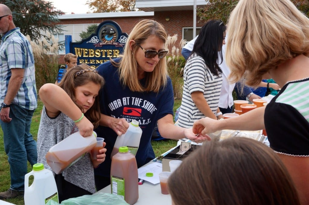 Rachel Mathews (left) and her mom, Margie, pour cider from The Farmer's Cow at the Webster Hill farmers' market on Oct. 22. Photo credit: Ronni Newton