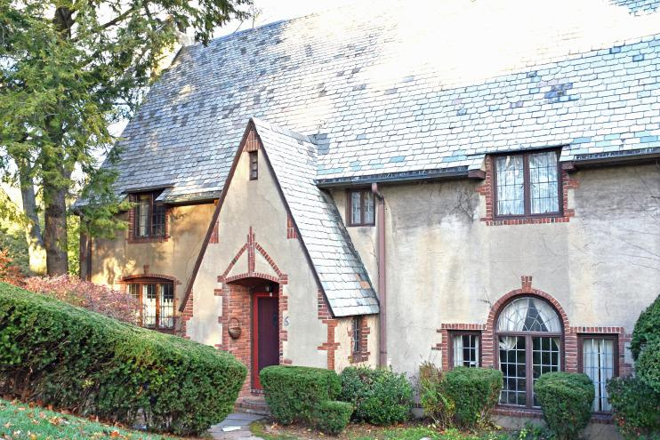 An interesting Tudor home with a stucco exterior, brick details, and a slate roof. Photo credit: Deb Cohen