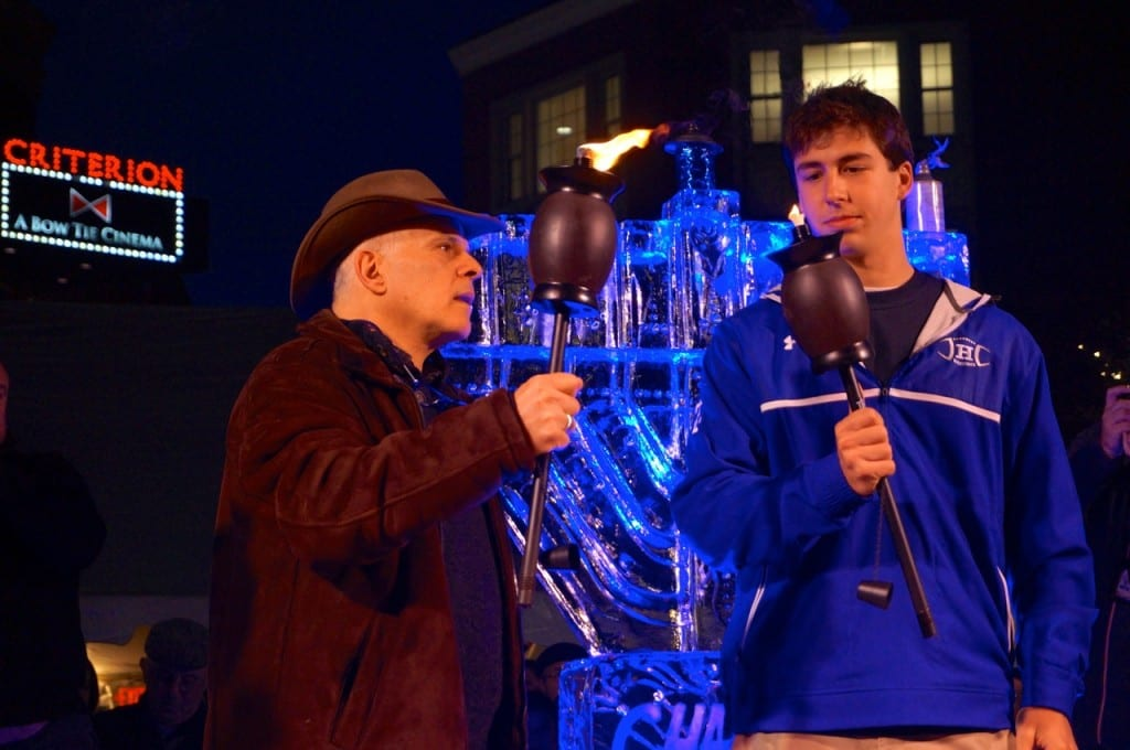 Dr. Michael Gutman passes lights the torch of Jordan Weinstock as part of 'Passing the Torch of Jewish Continuity' during the Chabad of Greater Hartford 'Fire on Ice' celebration. Photo credit: Ronni Newton