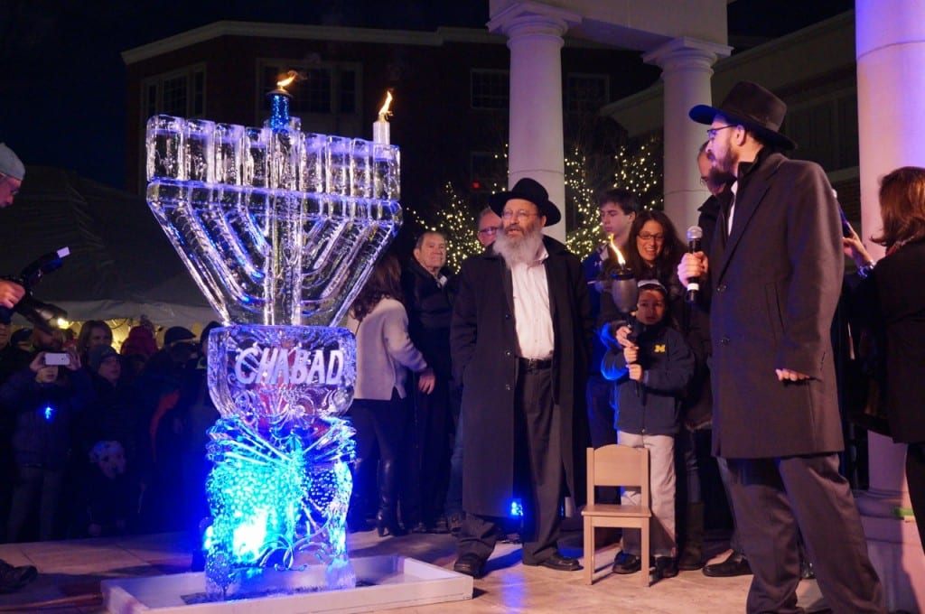 The first candle and the shamash of the menorah are lit. Chabad of Greater Hartford's 'Fire on Ice,' Dec. 6, 2015. Photo credit: Ronni Newton