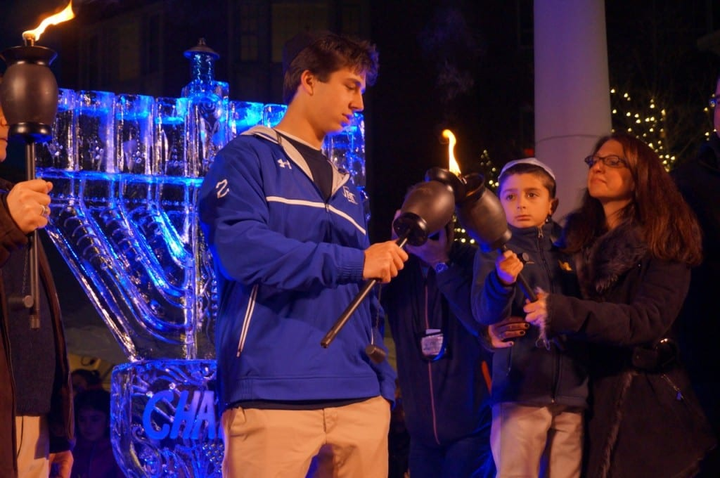 Jordan Weinstock passes the torch to the youngest member of the chain. Chabad of Greater Hartford's 'Fire on Ice,' Dec. 6, 2015. Photo credit: Ronni Newton