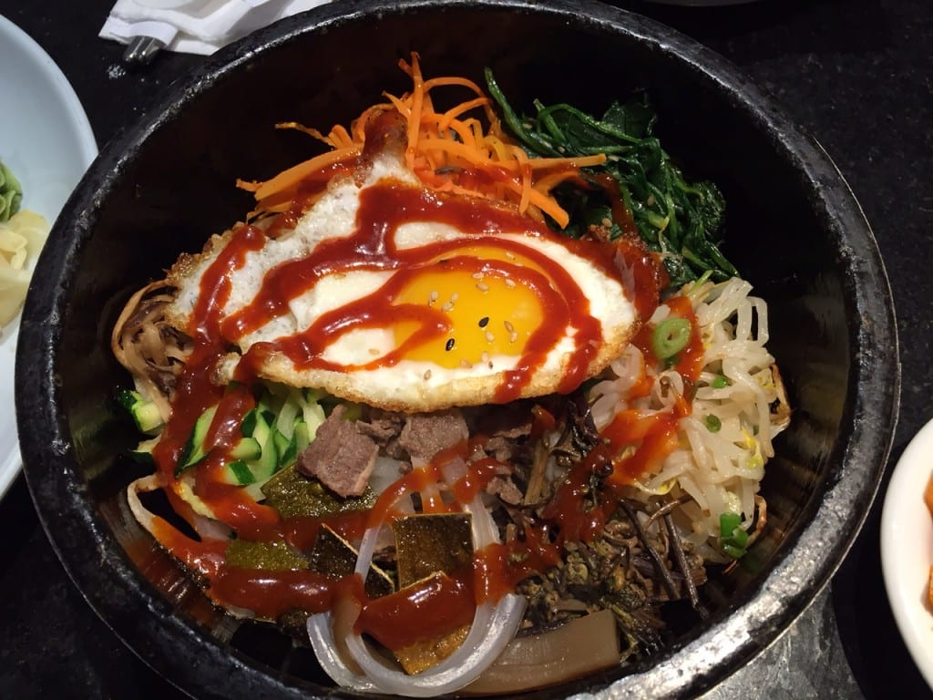 Bimimbap is a popular dish that includes steamed rice in a sizzling clay pot topped with beef, assorted stir-fried vegetables, and fried egg, topped with a red chili sauce. Photo credit: Ronni Newton