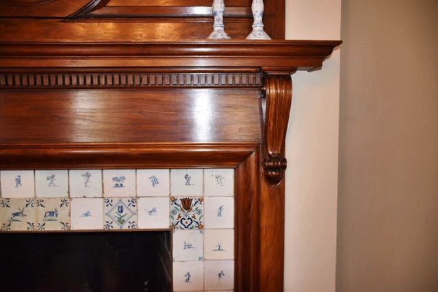 A close up of the elegant dining room mantel with Delft tile surround. Photo credit: Deb Cohen