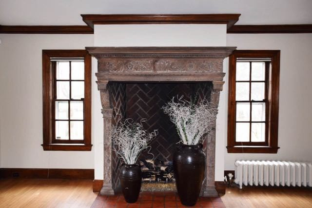 Massive stone fireplace surround in living room has intricate carved details. Photo credit: Deb Cohen