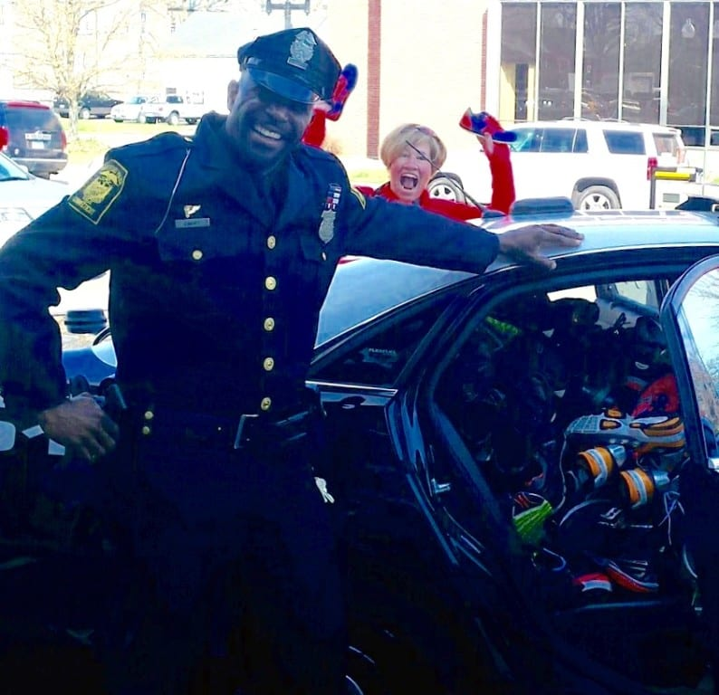 Fleet Feet owner Steph Blozy with Hartford Police Off. Jim Barrett help stuff a cruiser with shoes for the homeless on Saturday. Photo courtesy of Abby Moore