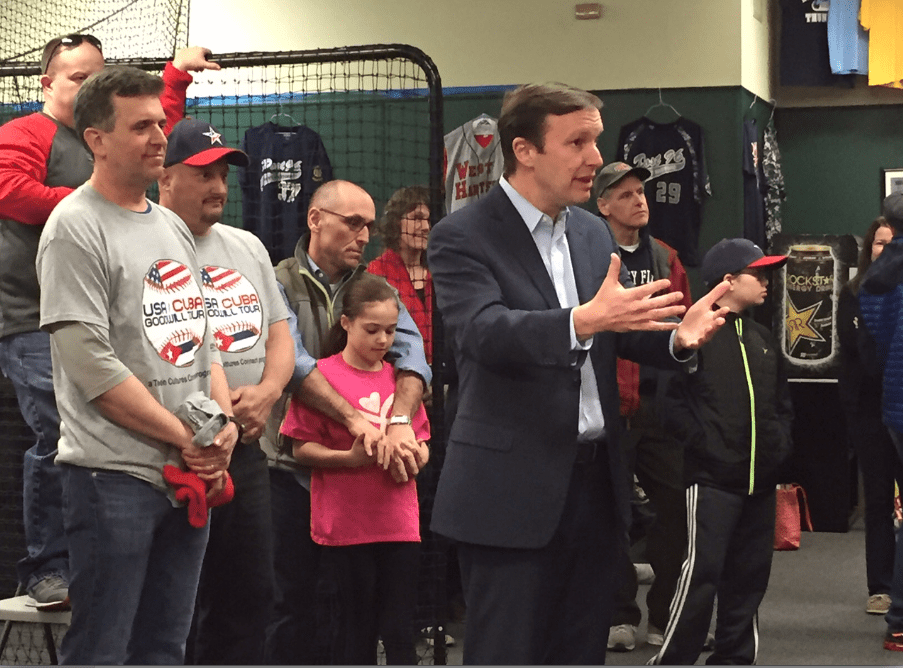 U.S. Sen. Chris Murphy speaks to the teens and their families at a send-off party Friday night. At left is Tim Brennan, organizer of the trip and an assistant coach of the team, and assistant coach Steve Meucci. Photo credit: Ronni Newton