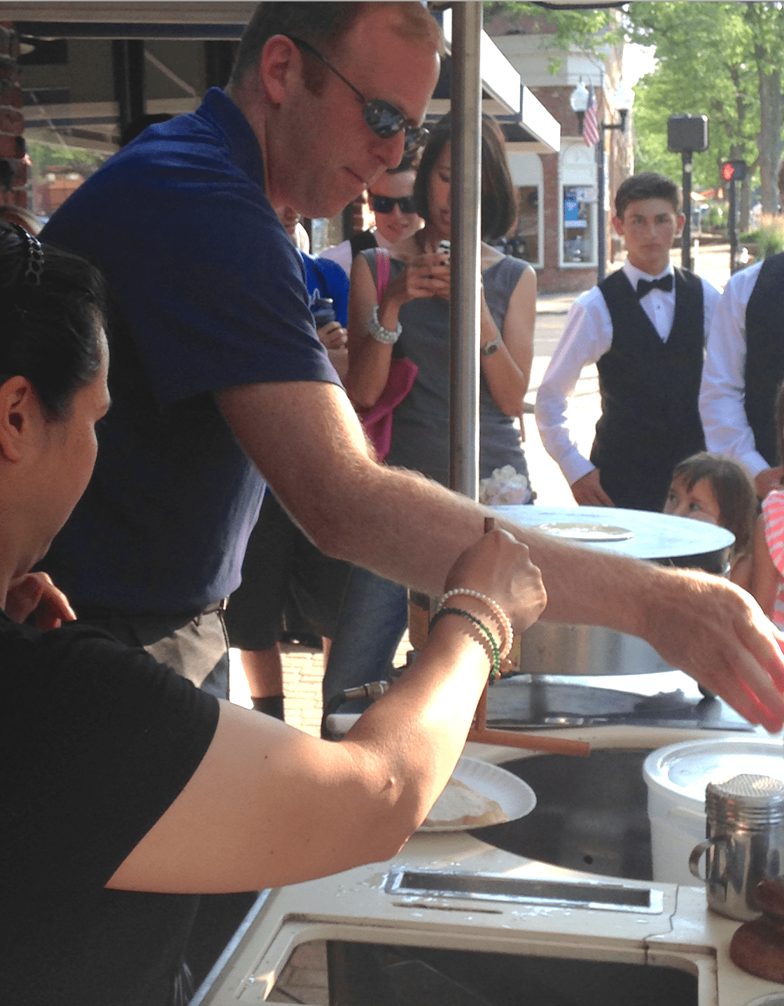 Rob Levine tries his hand at crepe making at the La Petite France crepe cart in West Hartford Center at the start of the Fashion Show event on June 23, 2016. Photo credit: Joy Taylor