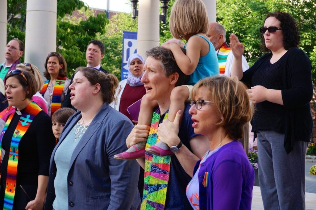 Shari Cantor (right) and area clergy hold hands and sing 'We Shall Overcome' at Wednesday night's vigil. Photo credit: Ronni Newton