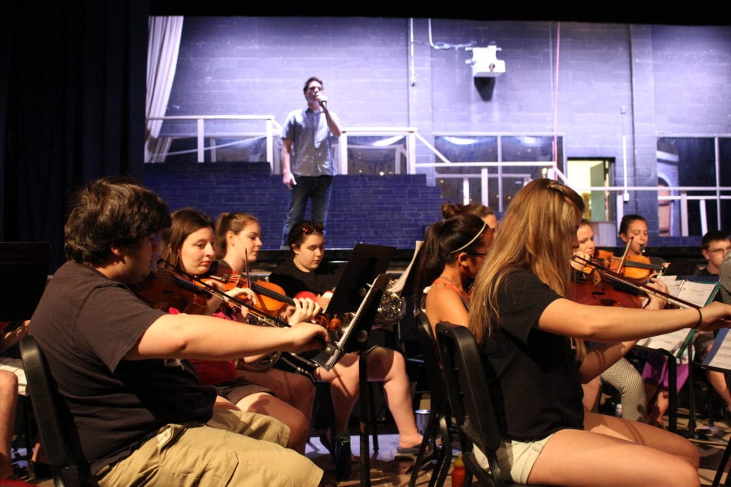 The 27-­member student orchestra rehearses with Ryan DeFranzo, who plays Beast. Photo credit: Emily Lafreniere