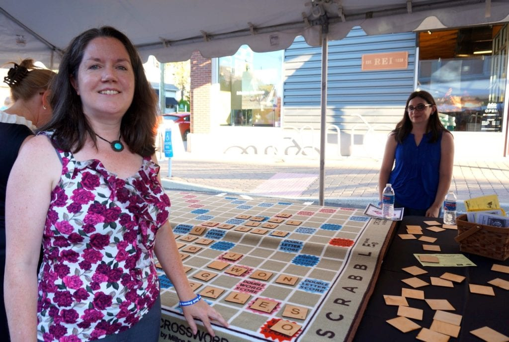 Noah Webster House Development Director Amy Boulton shows off the non-profit's giant Scrabble board. Taste of Blue Back Square and The Center. July 27, 2016. Photo credit: Ronni Newton