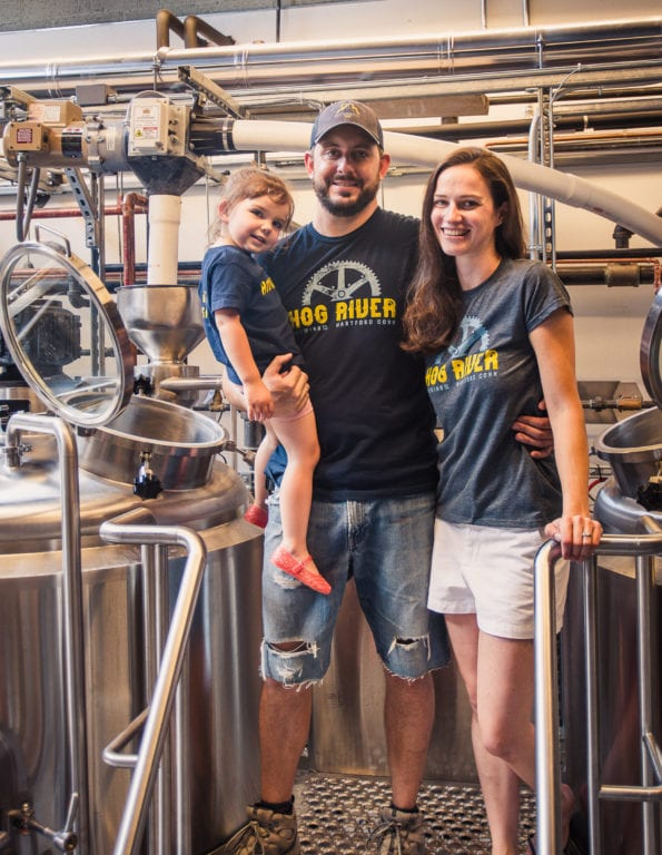 Ben (center) and Joy Braddock with their 2-year-old daughter, Ilya, at Hog River Brewing. Courtesy photo