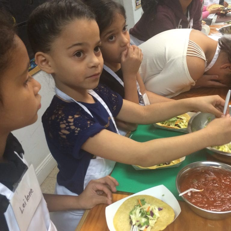 A young student makes tacos at a recent Growing Great Schools cooking class. Courtesy photo