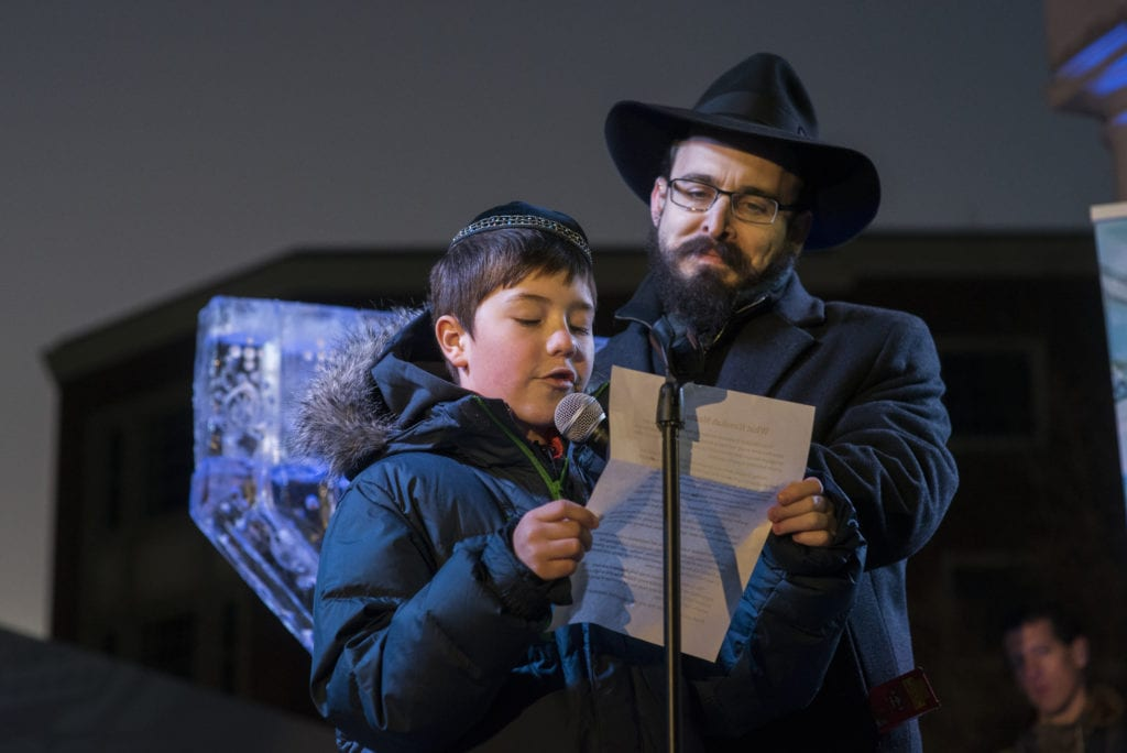 Chanukah Essay winner Mark Kirzon, age 10, reads his winning essay in front of the nearly 1,000 people, before the lighting of the Ice Menorah. At right is Rabbi Shaya Gopin of Chabad. Submitted photo
