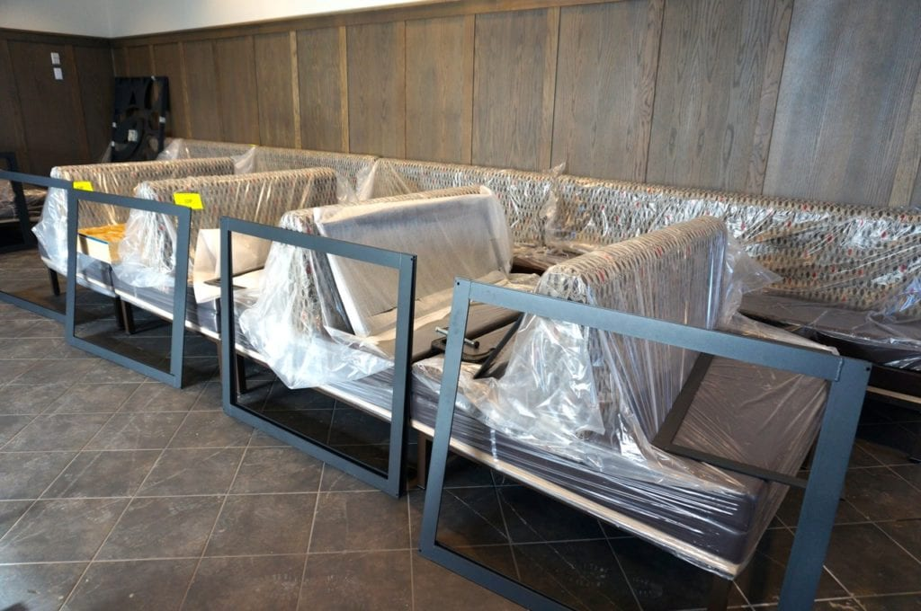 Seating is ready to be installed. The walls of the West Hartford Chick-fil-A are covered with distressed wood paneling. Photo credit: Ronni Newton