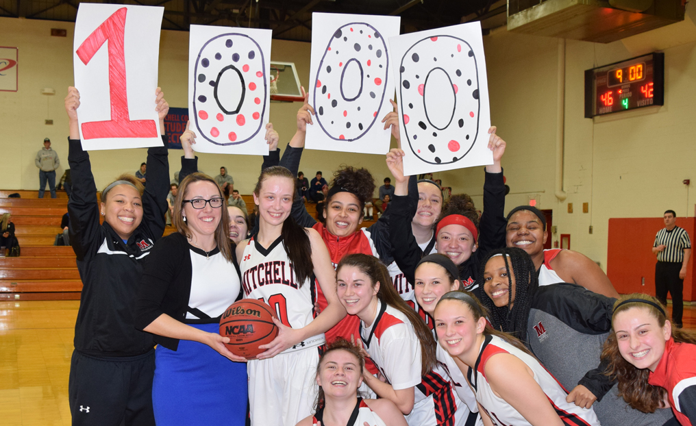 Jessica Shepherd (no. 10) is congratulated by her Mitchell College teammates after reaching the 1,000-point milestone on Valentine's Day. Courtesy of Mitchell College Sports Information Office
