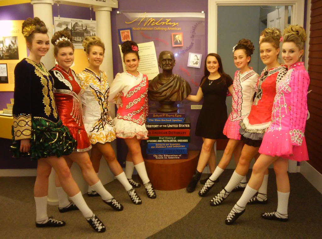 Dancers from the Coogan School of Irish Dance pose with a bust of Noah Webster in 2016. Submitted photo