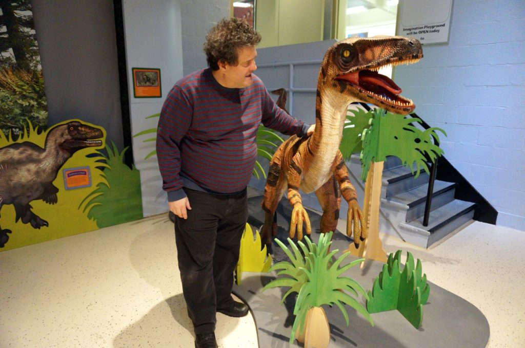 Exhibit designer Paul Orselli stands next to a classic 'Jurassic Park' dinosaur. Dinosaurs in Your Backyard: A Portal to Past Worlds exhibit. The Children's Museum, West Hartford. Photo credit: Ronni Newton