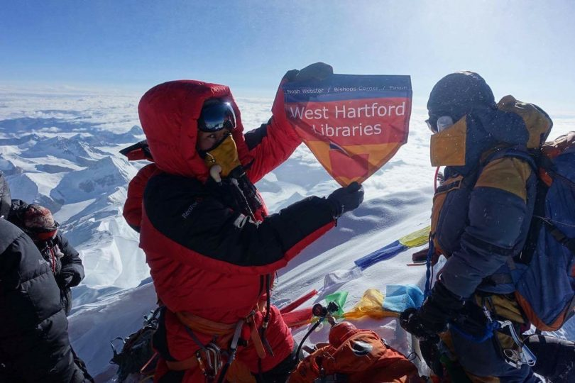 Lhakpa Sherpa holds up a'West Hartford Libraries banner as she summits Mt. Everest in 2017. Courtesy