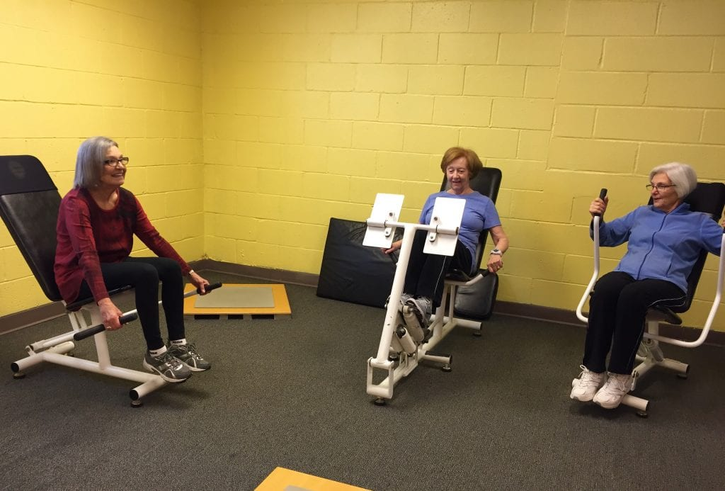 a group of women chat while working out on circuit training equipment that jeff roux purchased when a nearby curves location went out of business